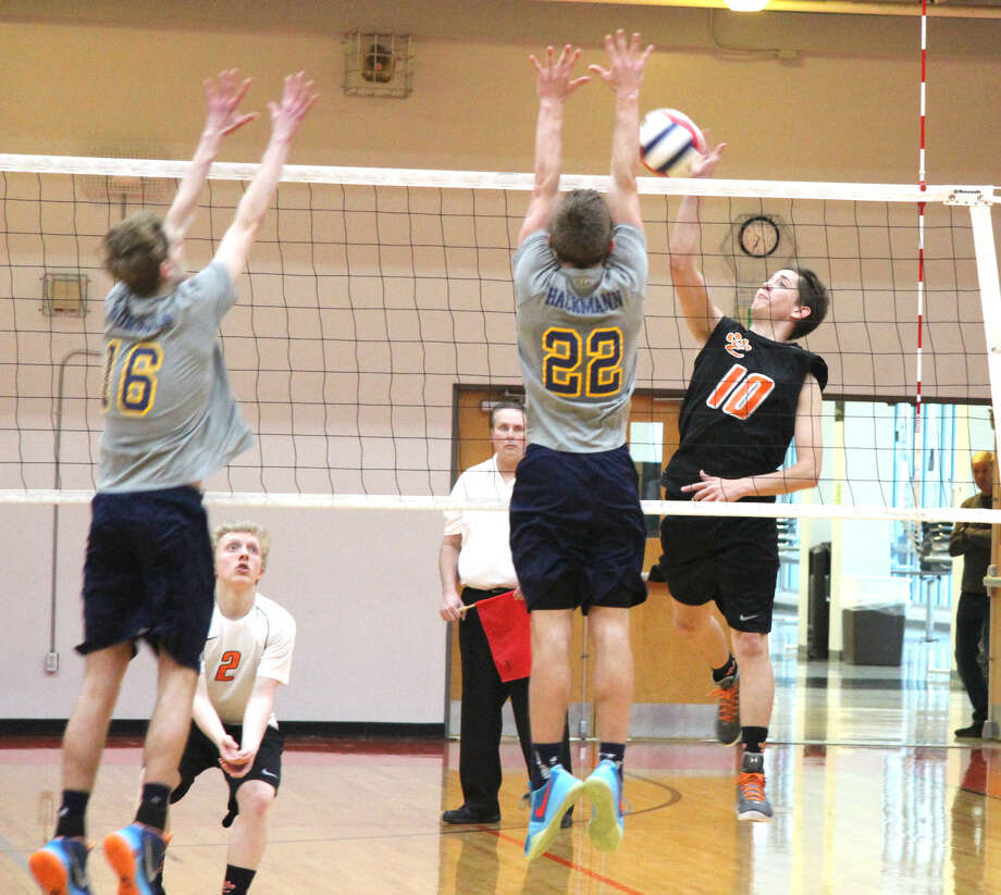 Edwardsville's Tommy Hartnagel tries to hit over the block of O'Fallon's Lucas Hackmann during Thursday's match at EHS.