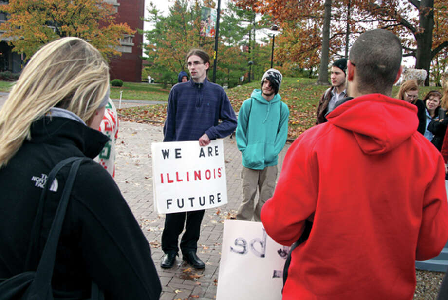 "Jordan Shaw, at right, an alumni of SIUE, holding a sign which reads, ""We Are Illinois' Future,"" speaks to a group of students and supporters of Occupy SIUE on the campus Wednesday. Photo: Marci Winters-McLaughlin/Intelligencer"