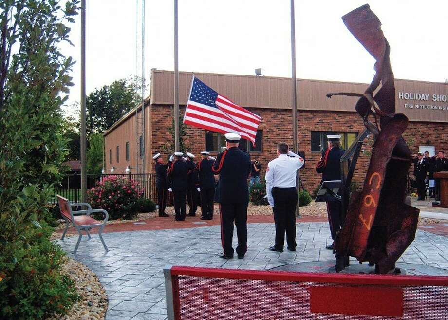 The Staunton Honor Guard performs the ceremonial retiring of the flag during the memorial held on Patriot Day at the Holiday Shores Firehouse Tribute Garden. More than 200 people turned out for the event held at sunset in honor of those who lost their lives on Sept. 11, 2001.