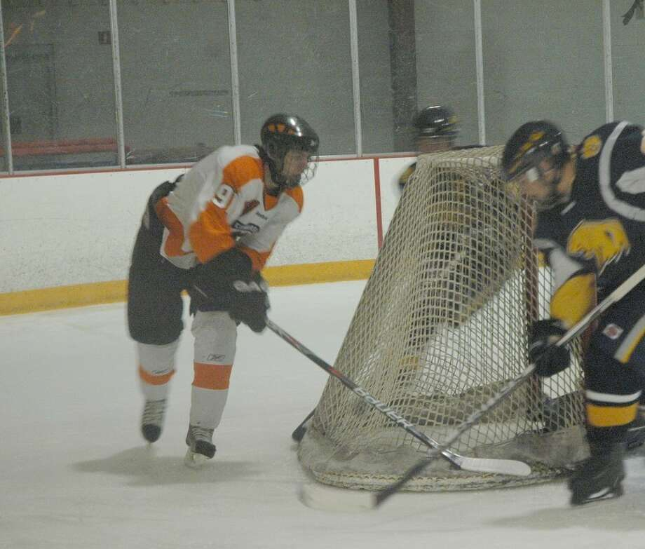 Edwardsville's Jon Weisner attempts a wrap-around with an O'Fallon defender charging on Tuesday at the East Alton Ice Arena.