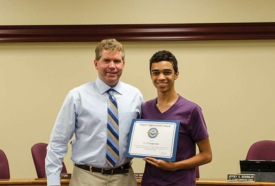 Edwardsville Mayor Hal Patton presents CJ Carpenter with the Mayor's Appreciation Award at a recent City Council meeting.