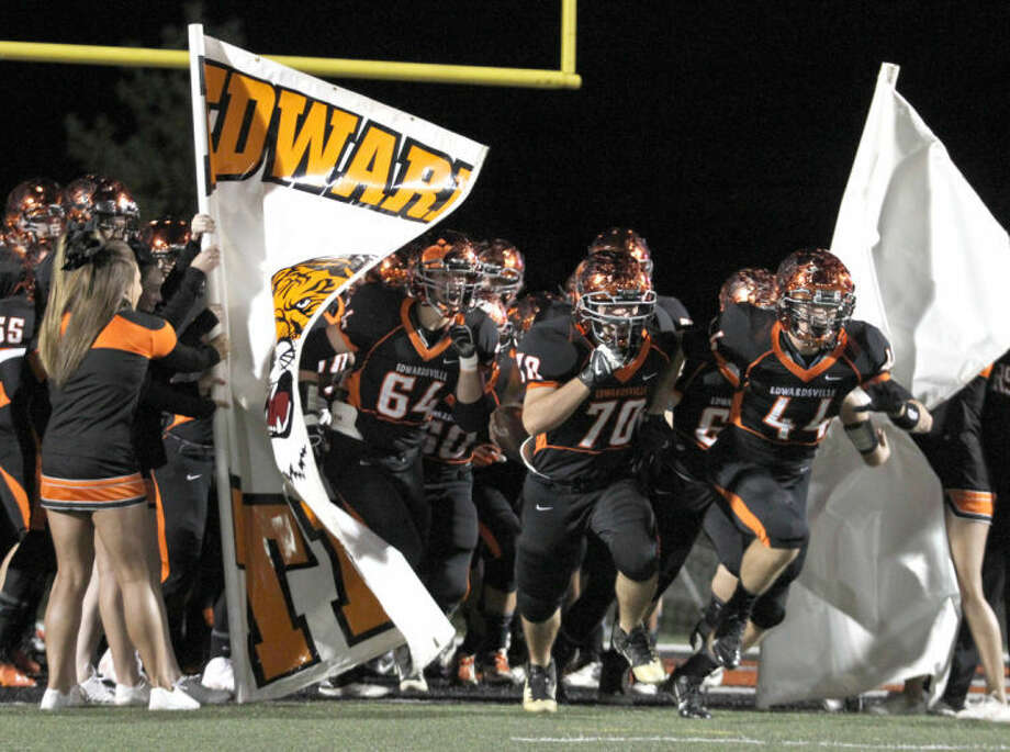 The Edwardsville Tiger football team breaks through the Tiger flag prior to Friday's Homecoming Game vs. Granite City led by seniors Kavan Weiss (64), Zach Ufert (70) and Hayden Schmidt (44). EHS hammered the Warriors 55-7 to earn at least a share of the Southwestern Conference for the first time since 2005. Photo: Shawn Semmler