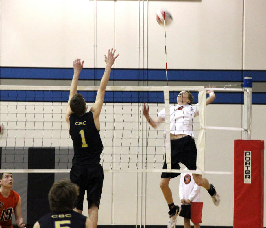 Edwardsville junior Nick Allen attempts to a make a kill over CBC's John Borgmeyer during Thursday's match at Liberty Middle School.