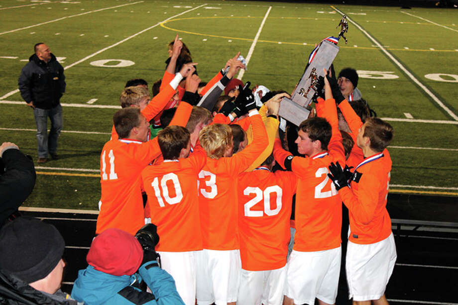 The Edwardsville Tiger boys' soccer team hoists the 2013 Illinois Class 3A state championship trophy on Saturday after a 2-1 title-game victory over the Wheeling Wildcats at Hoffman Estates High School.