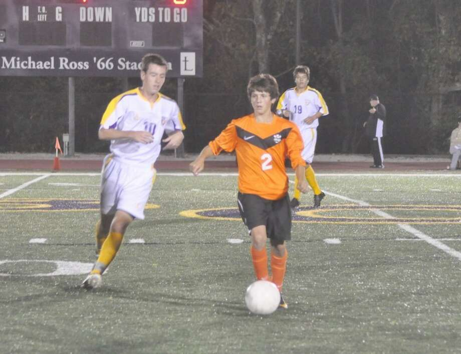 Edwardsville's Andrew Mullican, right, looks for an open teammate at midfield while CBC's Craig McLaurine gives chase. The Cadets defeated EHS 2-0 on Monday.