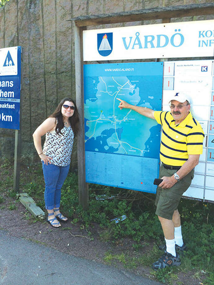 Lora Smallman with her father Gene next to a map of Vårdö, which is one of the island municipalities of the remote Åland Islands. Photo: For The Intelligencer