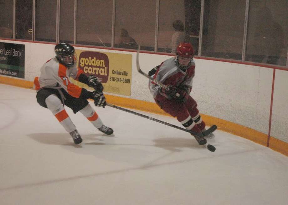 Edwardsville's Devon Fleck, left, deflects an Alton pass into the corner at the East Alton Ice Arena on Thursday. The Tigers defeated the Redbirds 4-2.