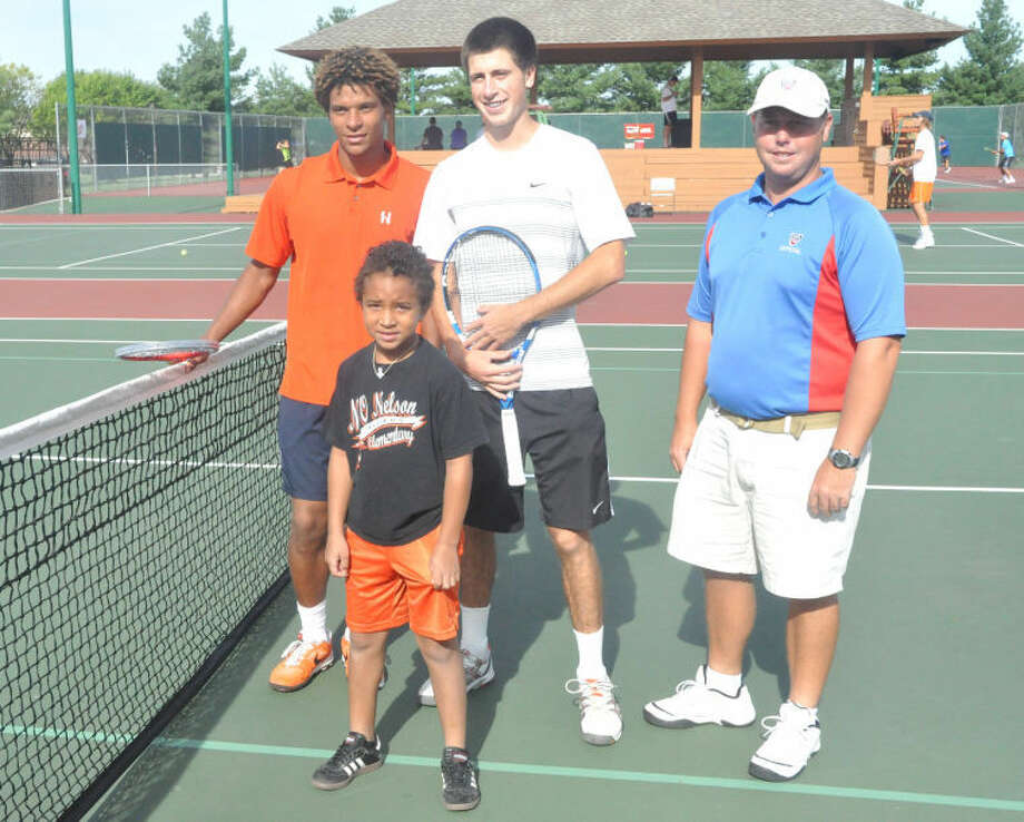 Edwardsville resident Aaron Hayes, 8, poses with University of Illinois' Julian Childers, left, William Mirkin, center, and a USTA official, right, on Sunday at the EHS Tennis Center during the qualifying tournament for the Edwardsville Futures.