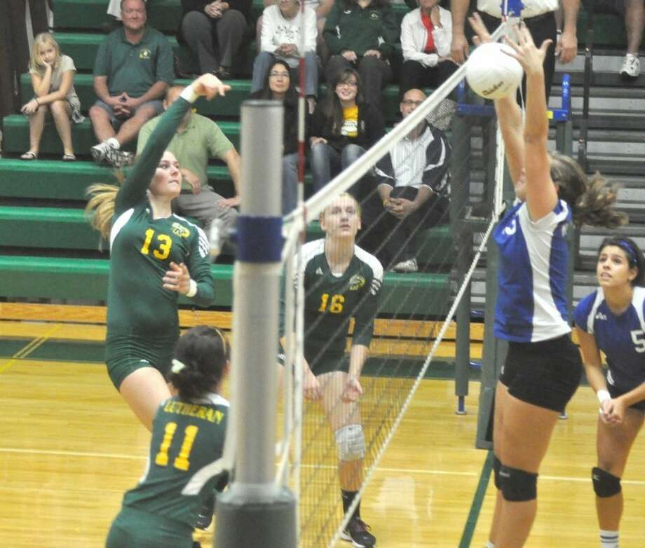 Metro-East Lutheran's Amy Best (13) earns a kill Monday at Thomas Hooks Gym vs. Alton Marquette.