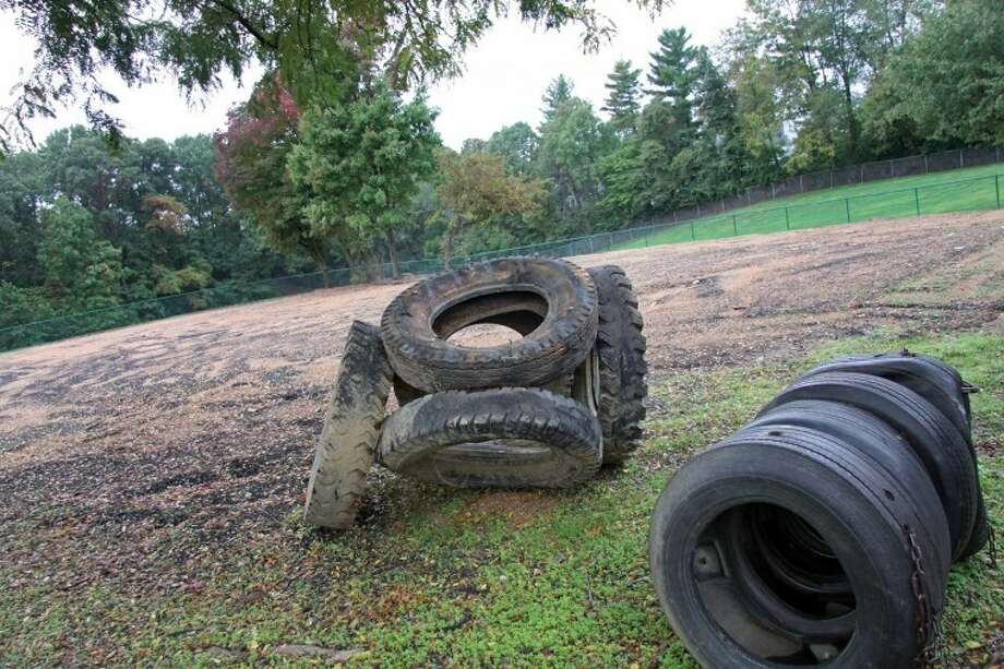 Discarded tires, once used for climbing on and through by many area children throughout the years, sit in a corner at the Edwardsville Township Playground site which is now bare