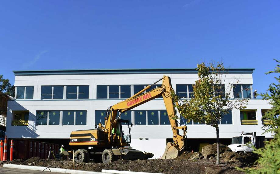 A construction crew works a Caterpillar backhoe Tuesday, Nov. 1 2016 at 500 Post Rd. East in Westport, Conn., the former headquarters of Terex which is being rebuilt for new tenants. Terex, Caterpillar and other major manufacturers of heavy construction equipment have been strained amid a slow rebound in the North American economy for infrastructure equipment that drives sales. Photo: Alexander Soule / Hearst Connecticut Media / Stamford Advocate
