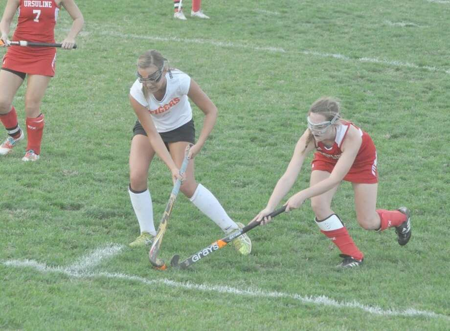 Tiger Abby Urbanek tries to dribble past a defender while keeping the ball in play.