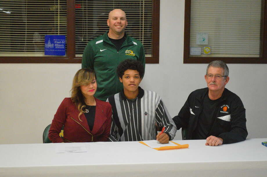 Metro-East Lutheran senior Teddy Fifer sits with his mother Sheila Minion and SWIC head coach Jay Harrington on his signing day. Looking on in the back row is MELHS Athletic Director Rob Stock.