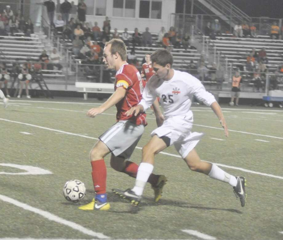 Edwardsville senior Colin Dorris battles with an Alton defender for the ball during first-half action at the District 7 Sports Complex. The Tigers celebrated Senior Night with a 1-0 win.
