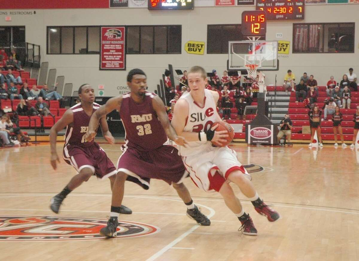 SIUE's Michael Messer, right, drives the ball against Robert Morris' Jordan Softley on Wednesday at the Vadalabene Center. The Cougars defeated the Eagles 85-61 in their home opener.