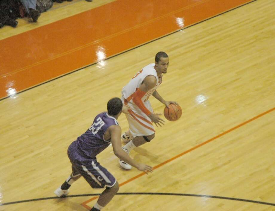 Edwardsville's Tre Harris, right, shields the ball from Collinsville's Devonta Crochrell in the first quarter of the Tigers' season opener at Lucco-Jackson Gymnasium on Friday.