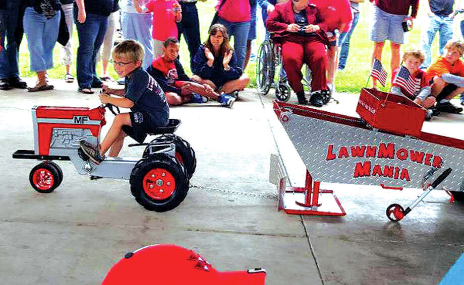 Four-year-old Jake Hampton pulls a 50-pound sled using pedal power at LawnMower Mania in 2012.  Youngsters are invited to participate in the pedal tractor pull on September 7. The event is broken down into three classes by the child's weight: 40 pounds and under, 41-60 pounds and 61-80 pounds.  Every child is a winner and receives a medal at the end of their pull. Photo: For The Intelligencer