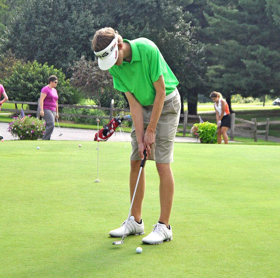 Edwardsville junior Cale Ambuehl sinks a putt Monday during practice at Oak Brook Golf Club.