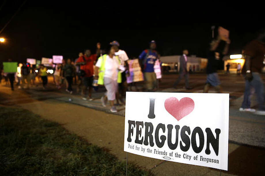 Protesters march Thursday, Aug. 21, 2014, in Ferguson, Mo. Protesters again gathered Thursday evening, walking in laps near the spot where Michael Brown was shot. Some were in organized groups, such as clergy members. More signs reflected calls by protesters to remove the prosecutor from the case. (AP Photo/Jeff Roberson) Photo: AP Photo/Jeff Roberson