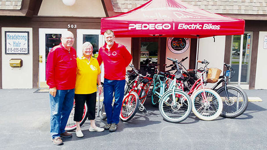 Dave, Leslie, and Archie Archer stand outside their Pedego Electric Bike Shop, located at 503 Saint Louis Street in Edwardsville. Bikes are available for purchase or rental. Photo: Adam McDonald/Intelligencer