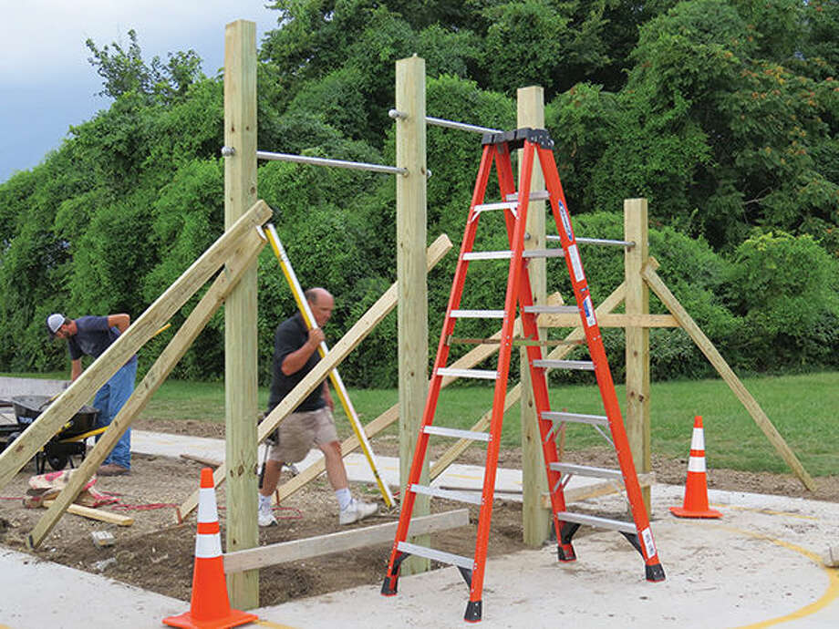 Workers are busy on the outdoor track at Our Health Club and Spa. The chin-up bar will be one of several exercise stations in the center of the track. Photo: Carol Arnett/Intelligencer