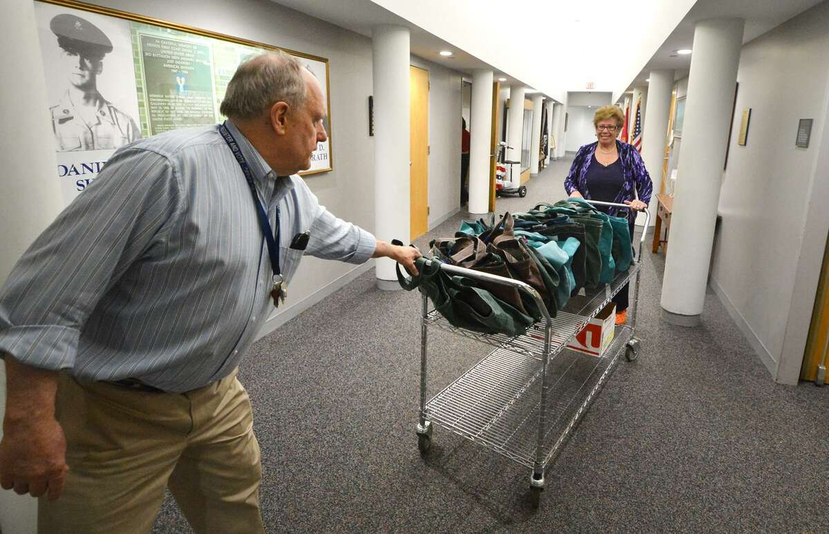 City of Norwalk's Stuart Wells, Democratic Registrar of Voters and Karen Doyle Lyons, Republican Registrar of Voters move a cart with all the moderators bags down a hallway at City Hall for moderator training on Monday April 25 2016