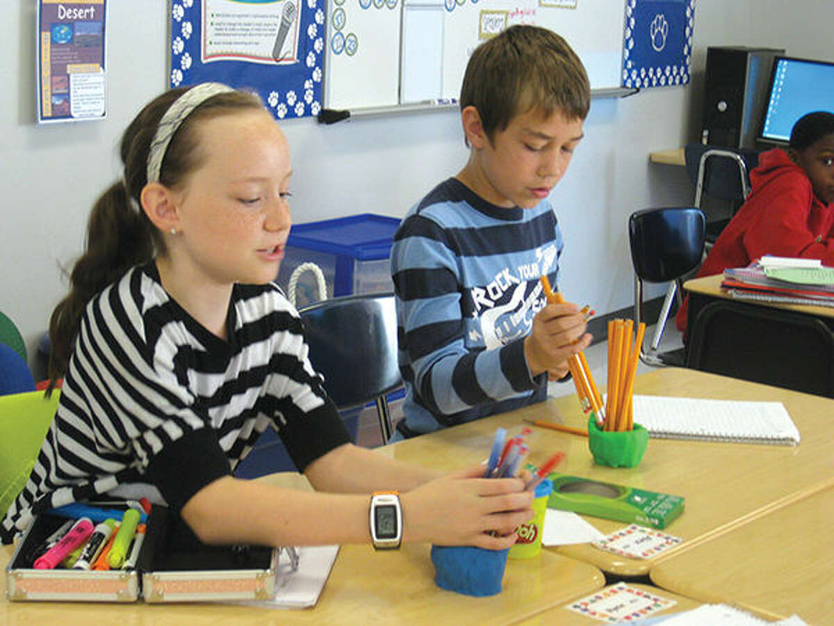 Albert Cassens Elementary School students Maryssa Dubach and Alex Allred place their pencils and pens in their clay holders in Matthew Aken's classroom.