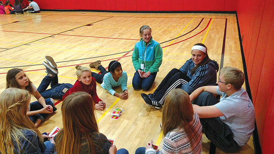 Lincoln and Liberty middle school students play cards with SIUE student athletes, at right, during a recent mentoring session.