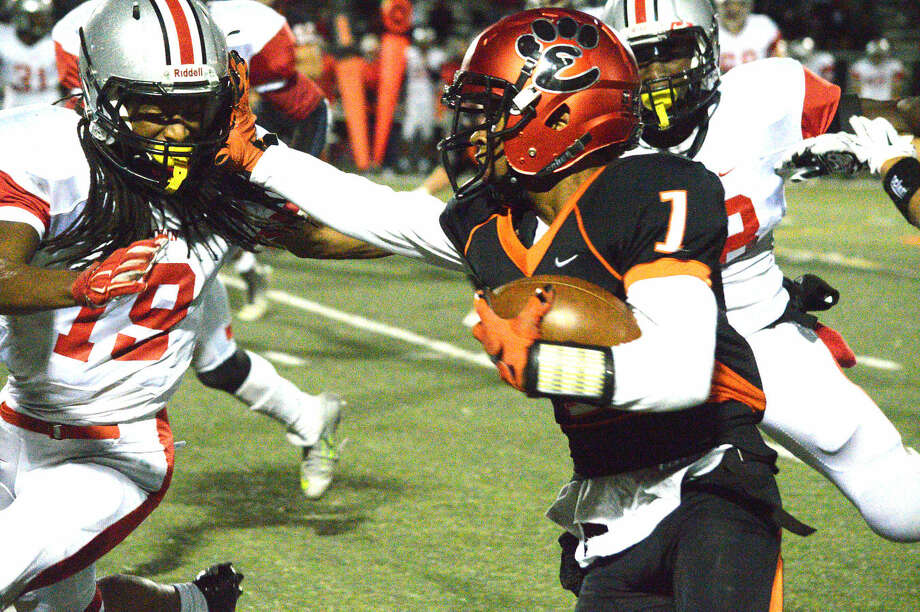 Edwardsville junior Daval Torres tries to push his way past Alton defender Simeon Brown during Friday's Southwestern Conference game at the District 7 Sports Complex.