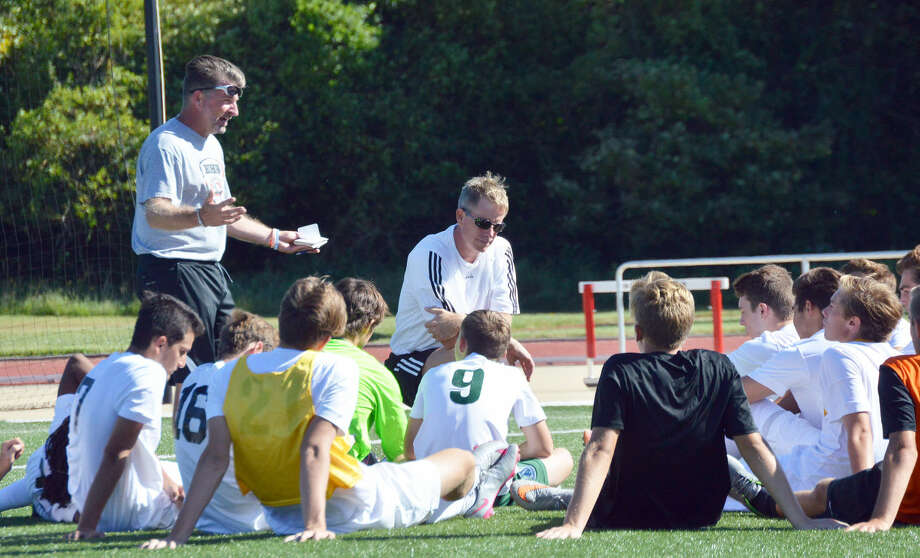 Edwardsville boys' soccer assistant coach Randy Chapman, standing, and coach Mark Heiderscheid, kneeling, talk to the team during halftime of the Dunlap game at SIUE.
