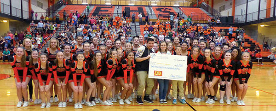 The Edwardsville High School Cheerleaders present a check for $2,500 to Todd Schultz and the Painting the Town Gold Campaign after a basketball game against the Harlem Wizards. Photo: For The Intelligencer