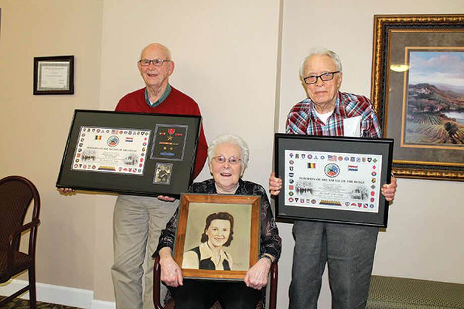 Richard Coyle, left, and Paul Scott hold the plaques they received as veterans of the Battle of Bulge. Dorothy Eden, center, holds a portrait of herself painted by a German prisoner of war.