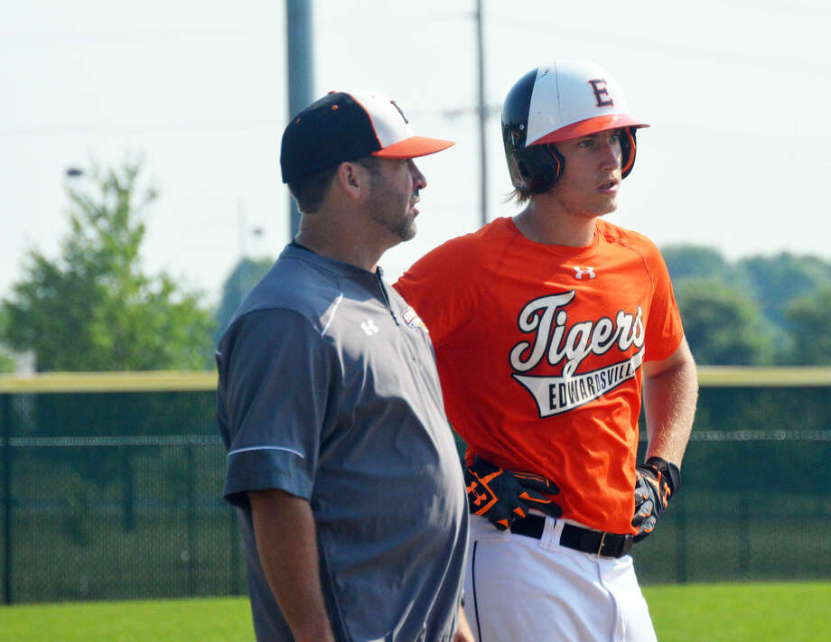 Edwardsville's Alec Mills, right, takes instruction from coach Tim Funkhouser while standing on third base during Sunday's game at Tom Pile Field.
