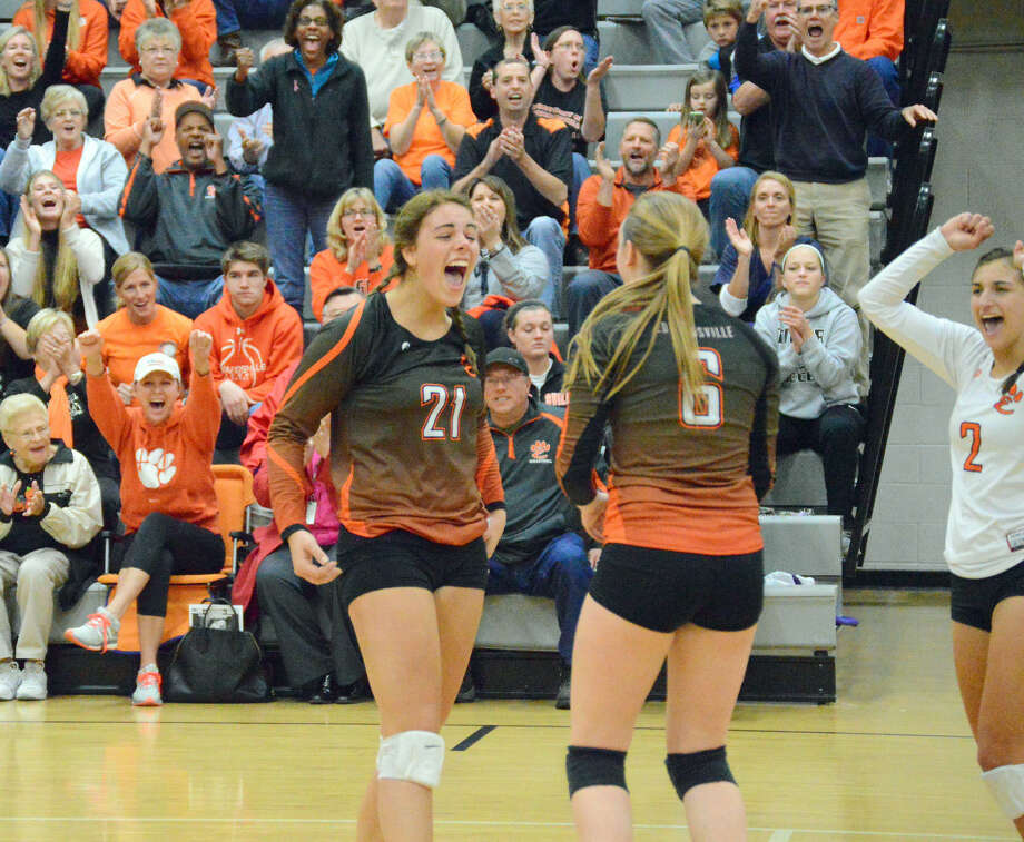 Edwardsville's Rachel Pranger, left, celebrates with Rachel Verdun, center, and Megan Woll after picking up a point during the regional championship match against O'Fallon.