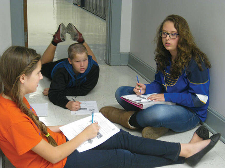Lincoln Middle School students, from left, Reagan Smith, Mason Taylor and Arianna Johnson, work on a CSI math activity. Photo: Julia Biggs/Intelligencer