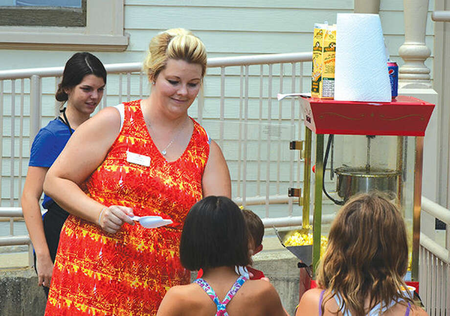 Lindley White, Operations Director of the Edwardsville Children's Museum, hands out popcorn at the museum's half birthday party in August. The party was a new event this year. Photo: Chris Schwent