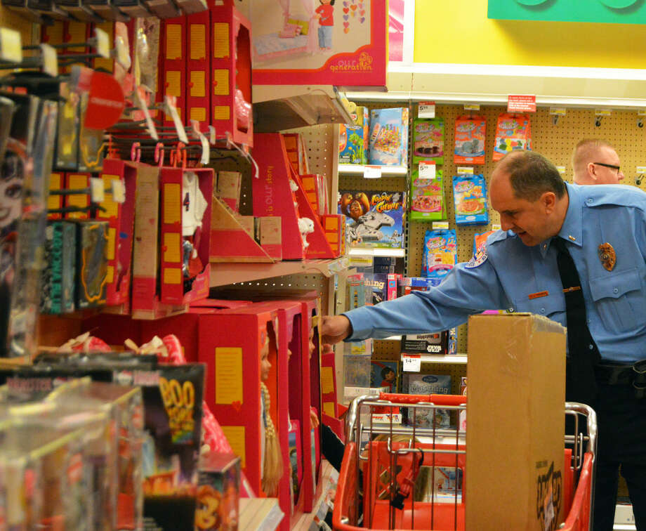 Edwardsville Police Lt. Charlie Kohlberg helps a young girl pick out a toy during Saturday's Christmas with a Cop at Target.