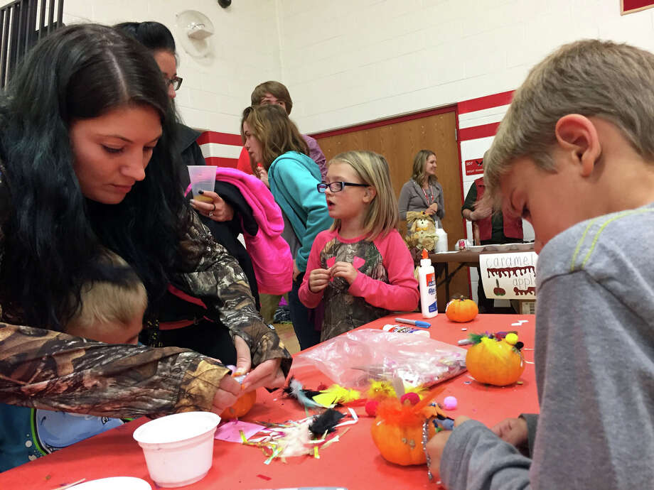 Families work to decorate the children's pumpkins. Children were able to use jewels, stickers, feathers and other craft supplies to decorate their pumpkin. Photo: Submitted Photo