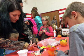 Families work to decorate the children's pumpkins. Children were able to use jewels, stickers, feathers and other craft supplies to decorate their pumpkin.