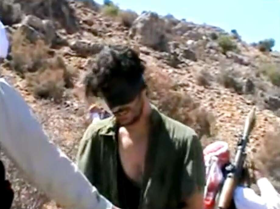 In this image taken from undated video posted to YouTube, American freelance journalist Austin Tice, who had been reporting for American news organizations in Syria until his disappearance in August 2012, prays in Arabic and English while blindfolded in the presence of gunmen. The Associated Press could not independently confirm the origin or the content of the clip, but the Tice family released a statement to several media outlets confirming it was their son in the video. Although the video footage shows a group of captors dressed and behaving like Islamic extremists, the clip lacks the customary form of jihadist videos. Previous reports have indicated that Tice is in Syrian government custody. (AP Photo) Photo: TEL / YouTube