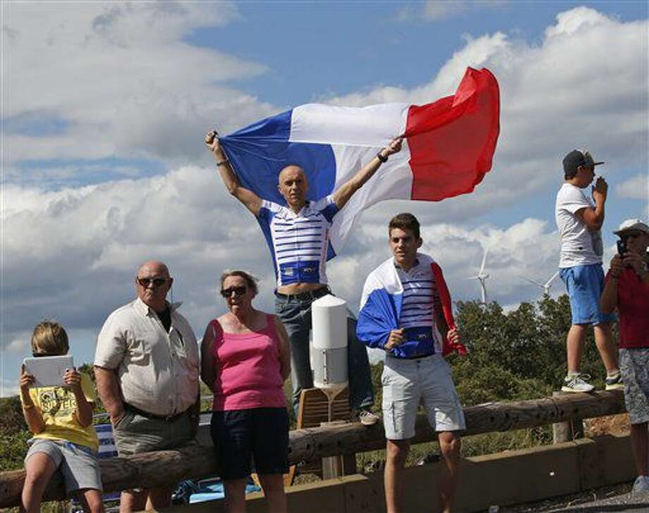 A man waves the French flag as he waits for the pack to pass during the eleventh stage of the Tour de France cycling race over 162.5 kilometers (100.7 miles) with start in Carcassonne and finish in Montpellier, France, Wednesday, July 13, 2016. (AP Photo/Christophe Ena) Photo: Christophe Ena