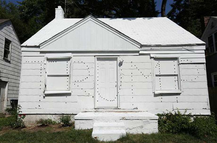 This photo taken July 12, 2016, shows a new project by Ryan Mendoza, an artist previously known for using an abandoned Detroit home for art, who has built a new project using two abandoned homes on either side of an occupied home. The artist has taken the homes that sit empty and has painted them white and then punched holes in the homes to spell Trump on one and Clinton on the other. At night the lights that he installed into the holes illuminate and the message he wants to convey is that there is a lack of political choice with Clinton and Trump. In addition, this signifies the state of America in the middle of this political campaign. (Regina H. Boone/Detroit Free Press via AP) Photo: Regina H. Boone