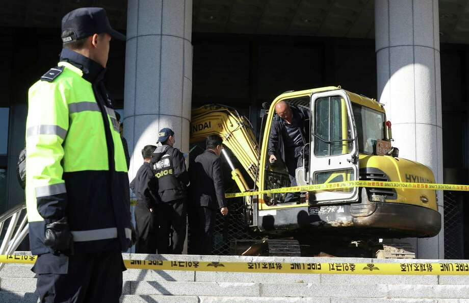 Police officers examine an excavator after a man rammed into a gate near a Seoul prosecutors' office in Seoul, South Korea, Tuesday, Nov. 1, 2016. Police detained  the man. The man later told investigators he tried to meet and help the woman with her death because she told reporters she deserves death. (Kim Do-hoon/Yonhap via AP) Photo: Kim Do-hoon, SUB / Yonhap