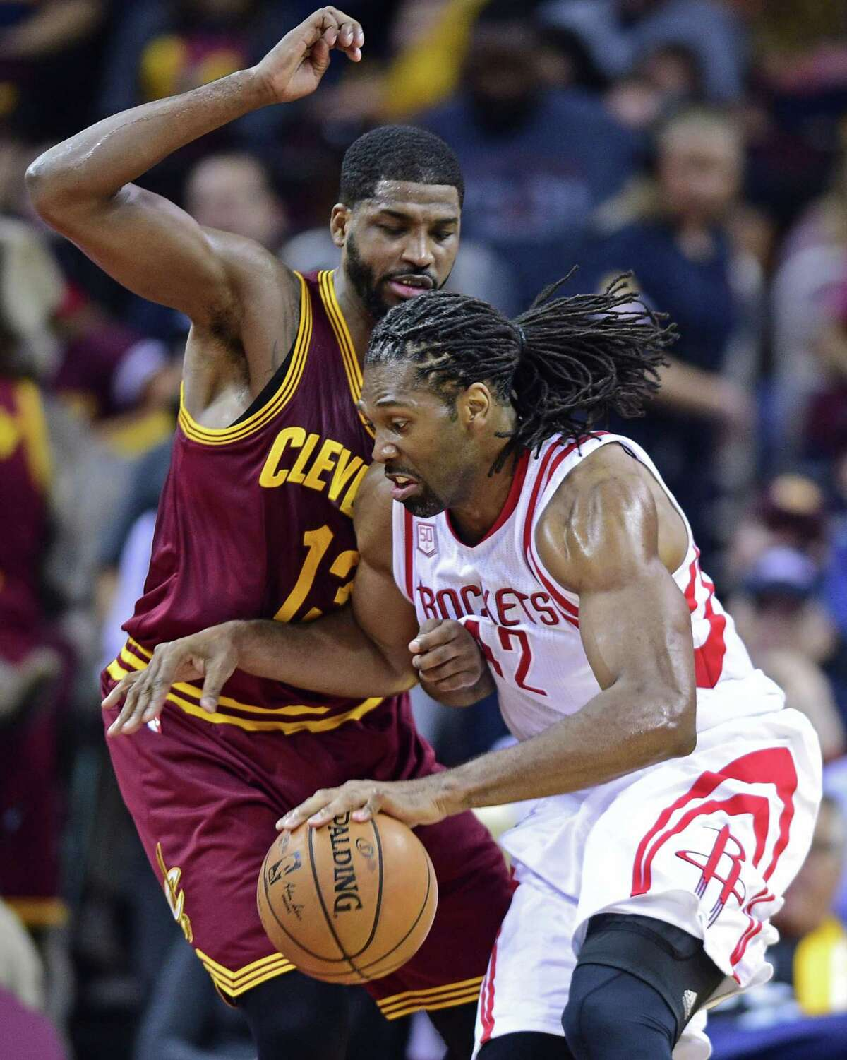 Houston Rockets forward Nene (42) drives on Cleveland Cavaliers forward Tristan Thompson (13) in the first half of an NBA basketball game Tuesday, Nov. 1, 2016, in Cleveland. (AP Photo/David Dermer)