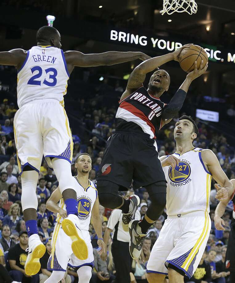 Portland Trail Blazers' Damian Lillard (0) shoots between Golden State Warriors' Draymond Green (23) and Zaza Pachulia, right, during the first half of a preseason NBA basketball game Friday, Oct. 21, 2016, in Oakland, Calif. (AP Photo/Ben Margot) Photo: Ben Margot, Associated Press