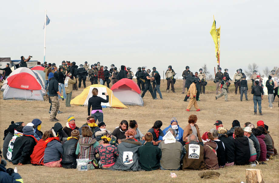 FILE - In this Oct. 27, 2016 file photo, Dakota Access Pipeline protesters sit in a prayer circle at the Front Line Camp as a line of law enforcement officers make their way across the camp to remove the protesters and relocate to the overflow camp a few miles to the south on Highway 1806 in Morton County, N.D. Members of more than 200 tribes from across North America have come to the Standing Rock Sioux Tribe's encampment at the confluence of the Missouri and Cannonball rivers since August, the tribe says. Estimates at the protest site have varied from a few hundred to several thousand depending on the day _ enough for tribal officials to call it one of the largest gatherings of Native Americans in a century or more. (Mike McCleary/The Bismarck Tribune via AP, File) Photo: Mike McCleary, MBO / The Bismarck Tribune