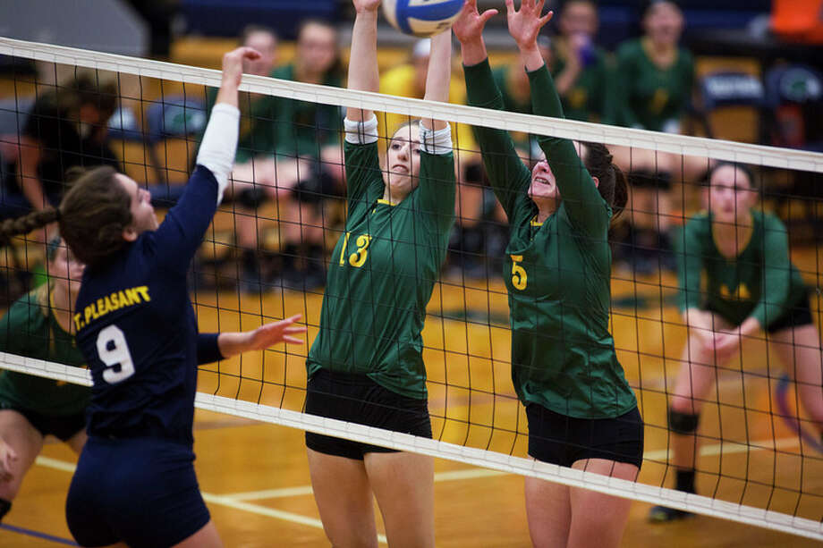 THEOPHIL SYSLO | For the Daily News Dow High School senior Jenna Livingston, center, and sophomore Isabel Velasquez, right, attempt to block Mt. Pleasant junior Carli Taylor, left, in the opening round of the Class A volleyball district at Heritage High School on Tuesday.