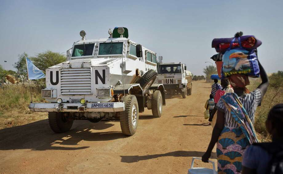 A U.N. armored vehicle is shown passing displaced people in South Sudan in 2013. The U.N. on Tuesday fired the commander of its peacekeepers there. Photo: Ben Curtis, STF / Copyright 2016 The Associated Press. All rights reserved.