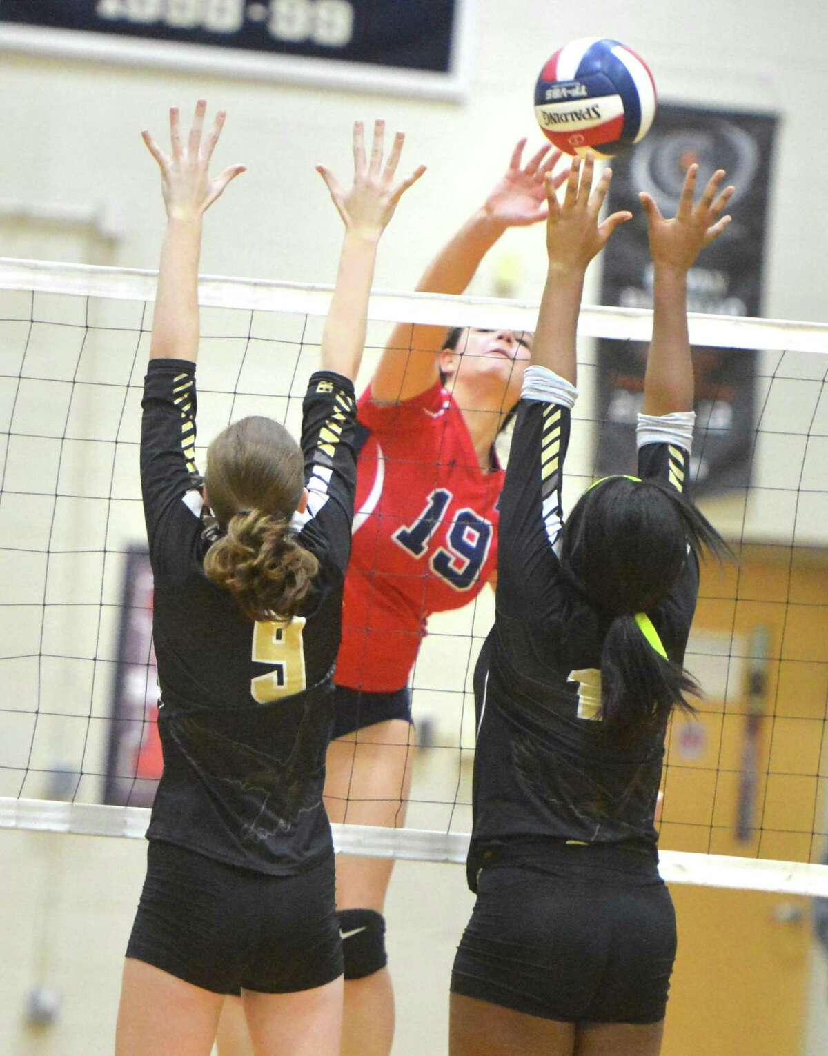 Brien McMahon's Meredith Pellegrino (19) gets the ball over two Trumbull defenders during Tuesday's match at Brien McMahon High School in Norwalk.