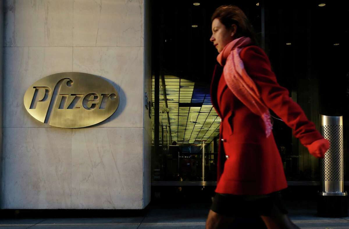 FILE - In this Monday, Nov. 23, 2015, file photo, a woman passes Pfizer's world headquarters, in New York. Pfizer reports financial results Tuesday, Nov. 1, 2016. (AP Photo/Mark Lennihan, File)